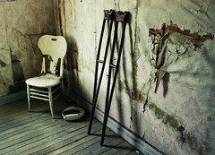 Crutches (Simple Insomnia) Tags: old wallpaper abandoned sepia dark bedroom chair montana peeling moody shadows furniture retro ghosttown lonely crutches garnet bedpan fixedshadows