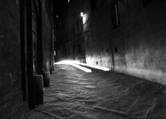 Siena (Peter Gutierrez) Tags: street light shadow bw italy white black streets building film blanco public architecture night contrast buildings dark square evening noche photo italian europe italia european nocturnal time nacht pavement negro sienna medieval sidewalk nighttime tuscany gutierrez siena toscana nuit bianco blanc nocturne notte italians italiano tuscan noire peter sienese gutierrez