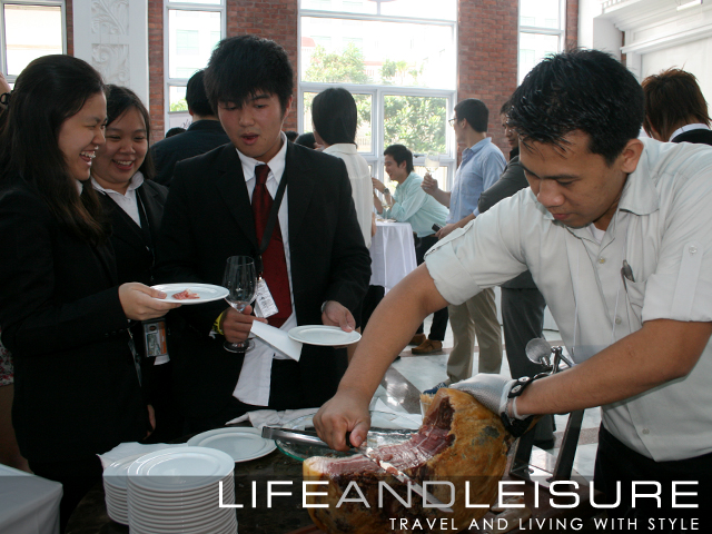 Students queue to get a taste of the freshly carved serrano ham served during the wine tasting event