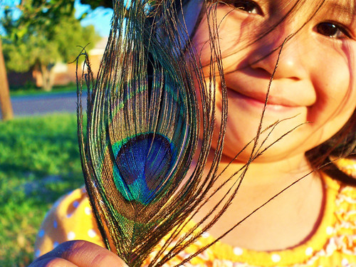 A young Tohono O'odham girl smiles and shows off a peacock feather.  The Tohono O'odham Community Action is working to create a healthy, sustainable and culturally-vital community for the Tohono O'odham Nation's 28,000 members.  Photo by Cheryl Maze Walker.