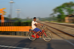 Pagi (Suryo Pras) Tags: street morning boy red portrait people motion blur bicycle speed train indonesia lens nikon focus slow cross candid rail center saturation kit 1855mm yogyakarta panning vr prambanan d3100