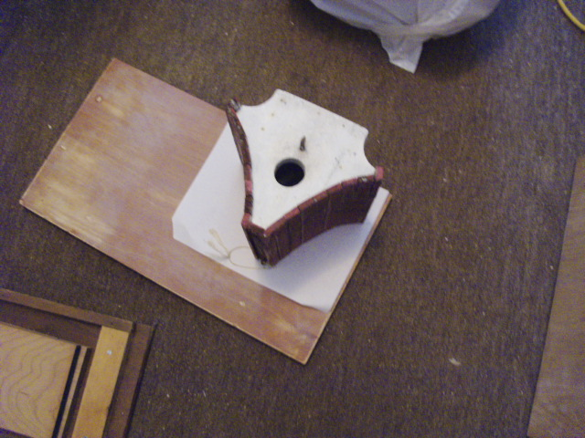 Marking one half of the old birdhouse onto paper...