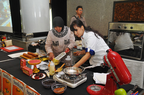 "Chef Ucu Sawitri invited one of the participants to work with her to prepare an ""Apple Banana Roll"" recipe using dehydrated potato flake, Washington apples, California raisins, and Washington apple juice."