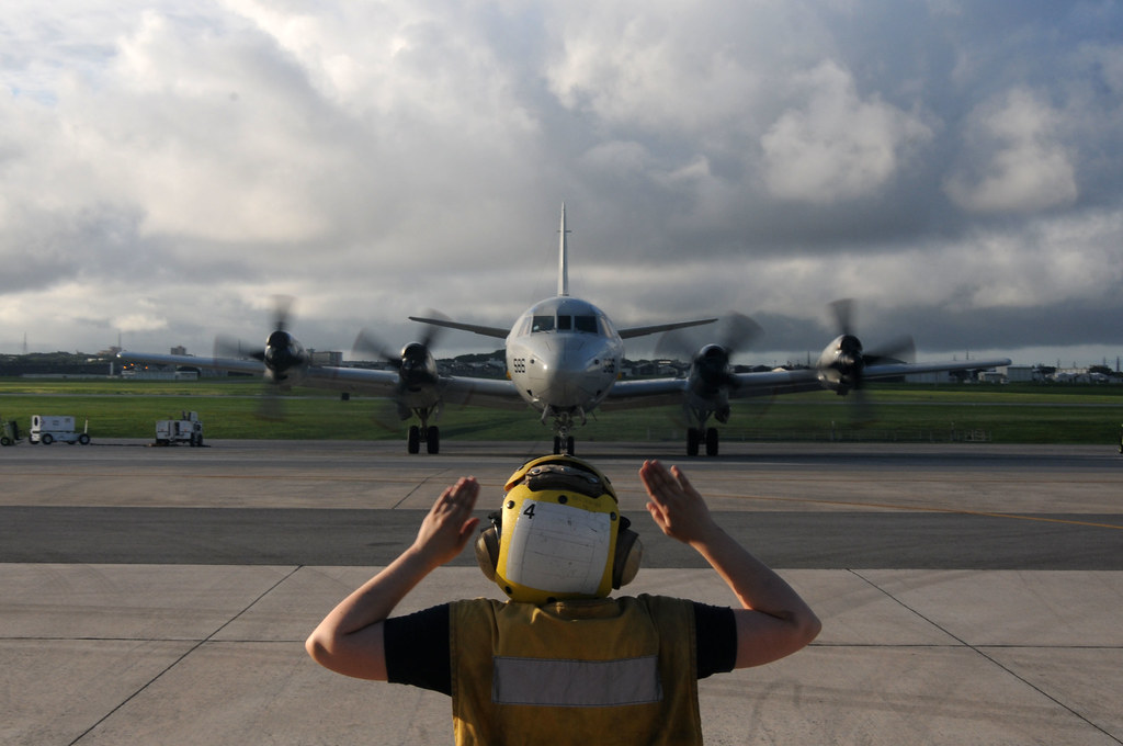 signals the flight line is clear and safe for taxing to pilots of a P-3C Orion aircraft