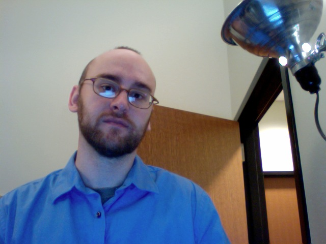 Man standing, wearing a blue shirt.