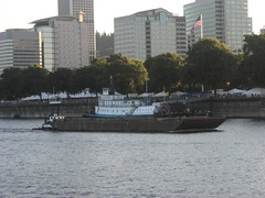 A tiny tugboat shoves a barge past the steamtug Portland
