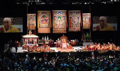His Holiness The 14th Dalai Lama addressing the crowd, double monitors, throne, monks on left, nuns on right, pavilion with mandala, offerings, security men, Kalachakra for World Peace, Verizon Center, Washington D.C., USA