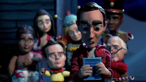 Group shot of Community's main characters in claymation form. Abed, who looks like simply an animated version of himself, is wearing a red plaid shirt and staring at a blue card he holds in both hands.