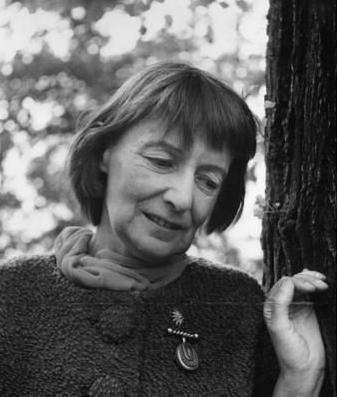 A black and white photo of Stevie Smith, a middle-aged white woman with chin-length hair, outside next to a tree. She is wearing a sweater with large buttons and is looking downward with a slight smile.