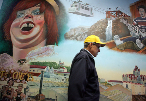 A visitor walks past a mural celebrating amusement parks at Playland-Not-At-The-Beach.