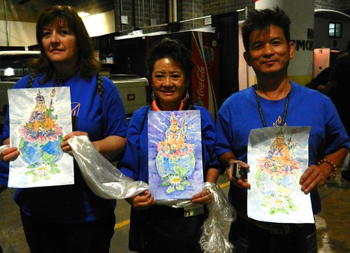 3 Pleased Volunteers holding original watercolor paintings of Padmasambhava, Guru Rinpoche, with khatas, as offerings, preparing for mandala offering to His Holiness 14th Dalai Lama of Tibet, Kalachakra for World Peace, Verizon Center, Washington D.C. USA by Wonderlane