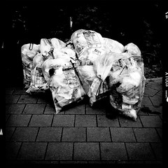 Waste (andersdenkend) Tags: road urban blackandwhite bw brick contrast trash square decay border frame arrow bags waste stark vignetting mll harsh tten dreck iphone gelbersack scke iphoneography hipstamatic wattslens nikeaodlxfilm