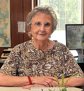 Barbara MacEwen, an elderly white woman white short grey hair and glasses, sits at a desk staring at the camera with a slight smile.