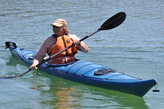 A man wearing an orange lifejacket in a blue kayak on a small lake in Northern Ontario.