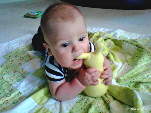 Baby playing with his Hug Me Slug by Elizabeth Ruffing, original art toys