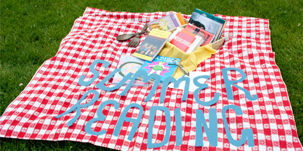 A photo of a red and white checkered picnic blanket lying on grass with a picnic basket and a pile of books on top of it