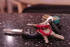 A ring of keys including a car key and a number of other keys with coloured tags.