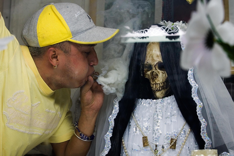 Blowing smoke to honor Saint Muerte