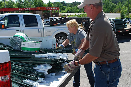 NRCS Soil Conservation Technician Pam Skidmore (l) helps an area producer load supplies.