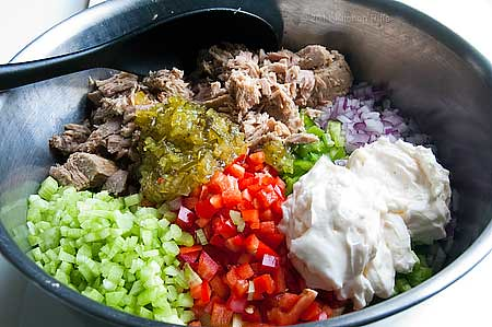 ingredients for Tuna Pasta Salad in bowl:  diced onions, celery, bell peppers, pickle relish, mayonnaise
