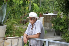 Man in Jelsa Portrait, Hvar Island (Alex E. Proimos) Tags: old portrait man guy hat shirt fence garden island glasses sad property croatia front tired worried worker worry lonely economic retired crisis struggle hvar croatian pensioner
