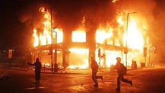 London police run past a building torched by youth in a rebellion in Tottenham in response to the cop killing of 29-year-old Mark Duggan. The rebellion has continued for a second night and spread to other cities. by Pan-African News Wire File Photos