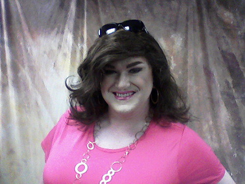 Femme-presenting person in a bright pink shirt and matching lipstick, with long wavy dark hair and sunglasses propped on her head, smiling broadly for the camera.