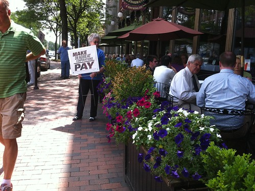 Newt Gingrich having lunch next to a protest