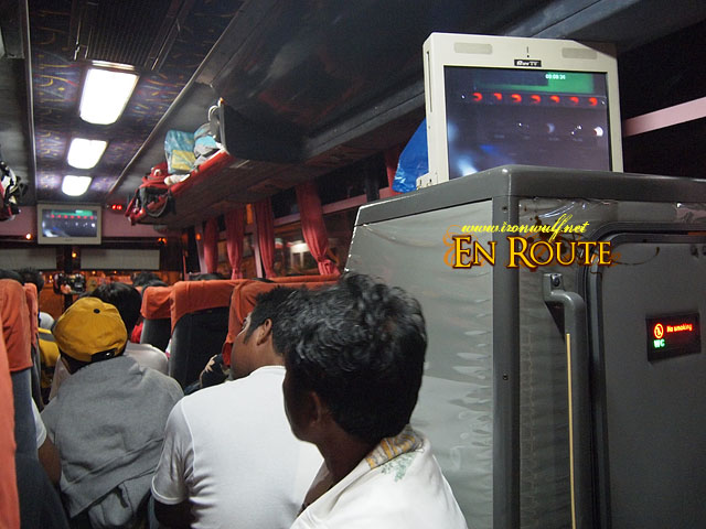 A packed bus with people seating at the aisle