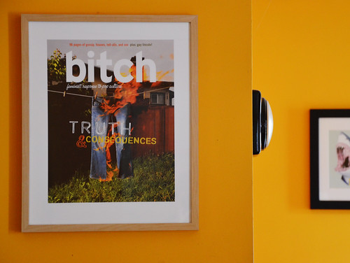 Truth & Consequences print hangs on an orange wall. The print depicts a pair of jeans on fire.