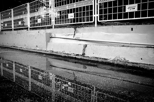 Reflection of the KTM station fence in a puddle of water