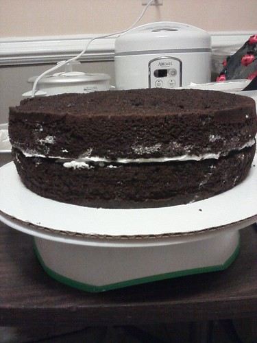 Stacking the bottom layer of the hopefully 2-tier choco cake.
