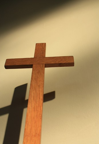Image of a small wooden cross casting a shadow on the wall