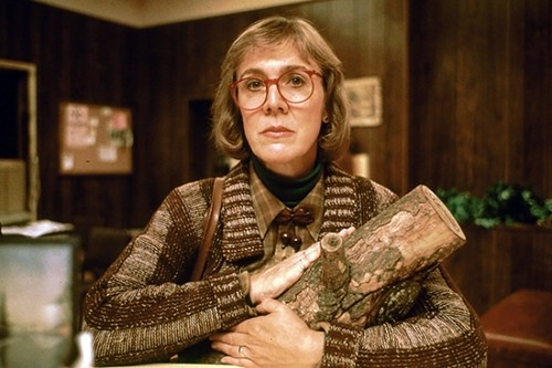 The Log Lady, a white woman wearing glasses, holds a small log in her arms and looks at the camera