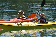 Two children, one in a red kayak, the other in a yellow kayak, paddling together.