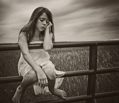 Pensive (Emily Bemily) Tags: sky blackandwhite girl field fence gate child sad naturallight barefoot disappointed pensive dslr whitedress thougthful
