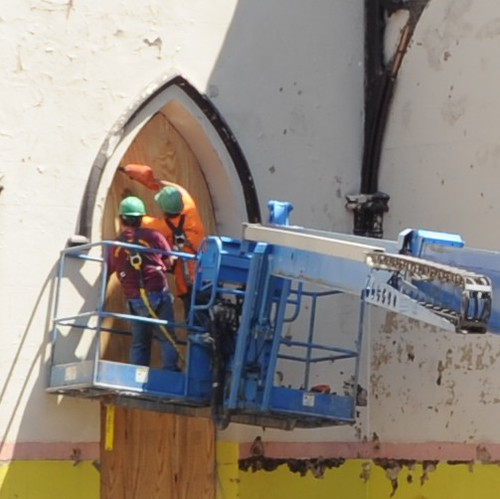 Workers nail plywood to protect the stained glass