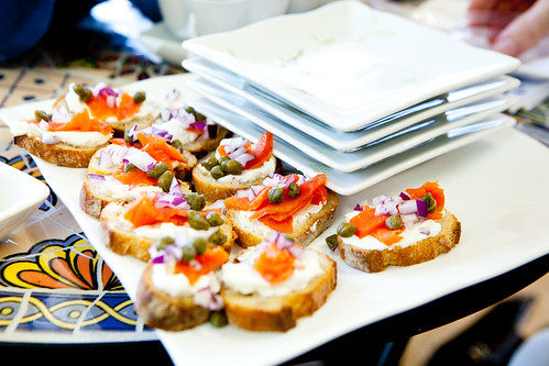Plate of open faced cream cheese and smoked salmon and capers sandwiches