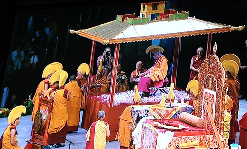 His Holiness the 14th Dalai Lama sitting in the middle of the Kalachakra mandala pavilion, prayers, strewing flowers, monks wearing gold hats & formal robes, his throne, from monitor, Verizon Center, Washington D.C., USA by Wonderlane