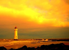 Sunset at New Brighton Lighthouse, (Tony Worrall Foto) Tags: uk light sunset sea england copyright beach nature sunshine weather clouds danger liverpool warning fire golden seaside rocks view natural northwest scenic birkenhead shore lit sunlit seashore attraction fireinthesky wirral newbrighton redskyatnight merseyside scouse newbrightonlighthouse perchrocklighthouse 2011tonyworrall