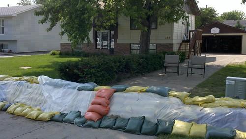 Orange sandbag steps to protect dike's plastic barrier