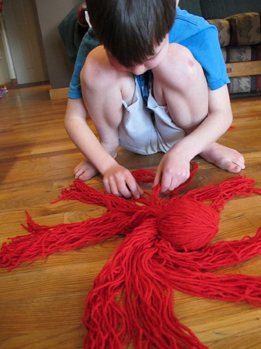S braiding the legs of his yarn octopus