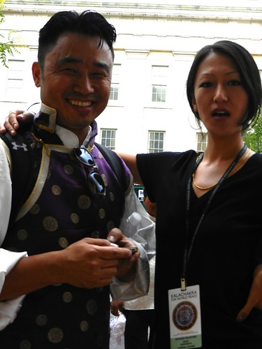 Striking a gentle pose, a Tibetan volunteer wearing a Kalachakra badge with her friend in his traditional updated purple and gold trim jacket and white shirt, Kalachakra for World Peace, Washington D.C., USA by Wonderlane