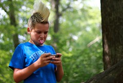 Liam sticking out tongue (Beth Duri) Tags: portrait silly tongue canon outdoors 50mm kid funny punk ipod child games mohawk picnik preteen makingface canon60d bethduri