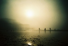 Fading Away (fotobes) Tags: light sea sun misty fog reflections sussex lomo lca xpro lomography sand brighton mood moody dusk crossprocess grain foggy silhouettes surreal atmosphere westpier faded lowtide grainy vignetting brightonbeach figures vignette murky muggy lastlight fadedbeauty fadingaway lomographychrome100 fotobes