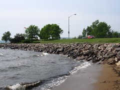 the lakeshore (ailie*) Tags: road street blue trees summer sky people brown lake green cars beach water grey duck sticks sand rocks waves cloudy streetlights sandy shoreline overcast shore wavy ailie breakwater northbay nipissing