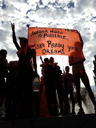 Protesters standing with a sign that reads 'another world is possible'