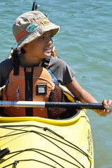 An Asian child wearing a brown hat, sitting in a yellow kayak on blue-green water in Northern Ontario.