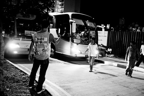 A traffic controller directing the waves of buses coming into the street.