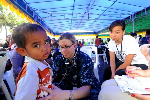 Lt. Stacy Dodt, a doctor embarked aboard the Military Sealift Command hospital ship USNS Mercy (T-AH 19), examines an Indonesian child
